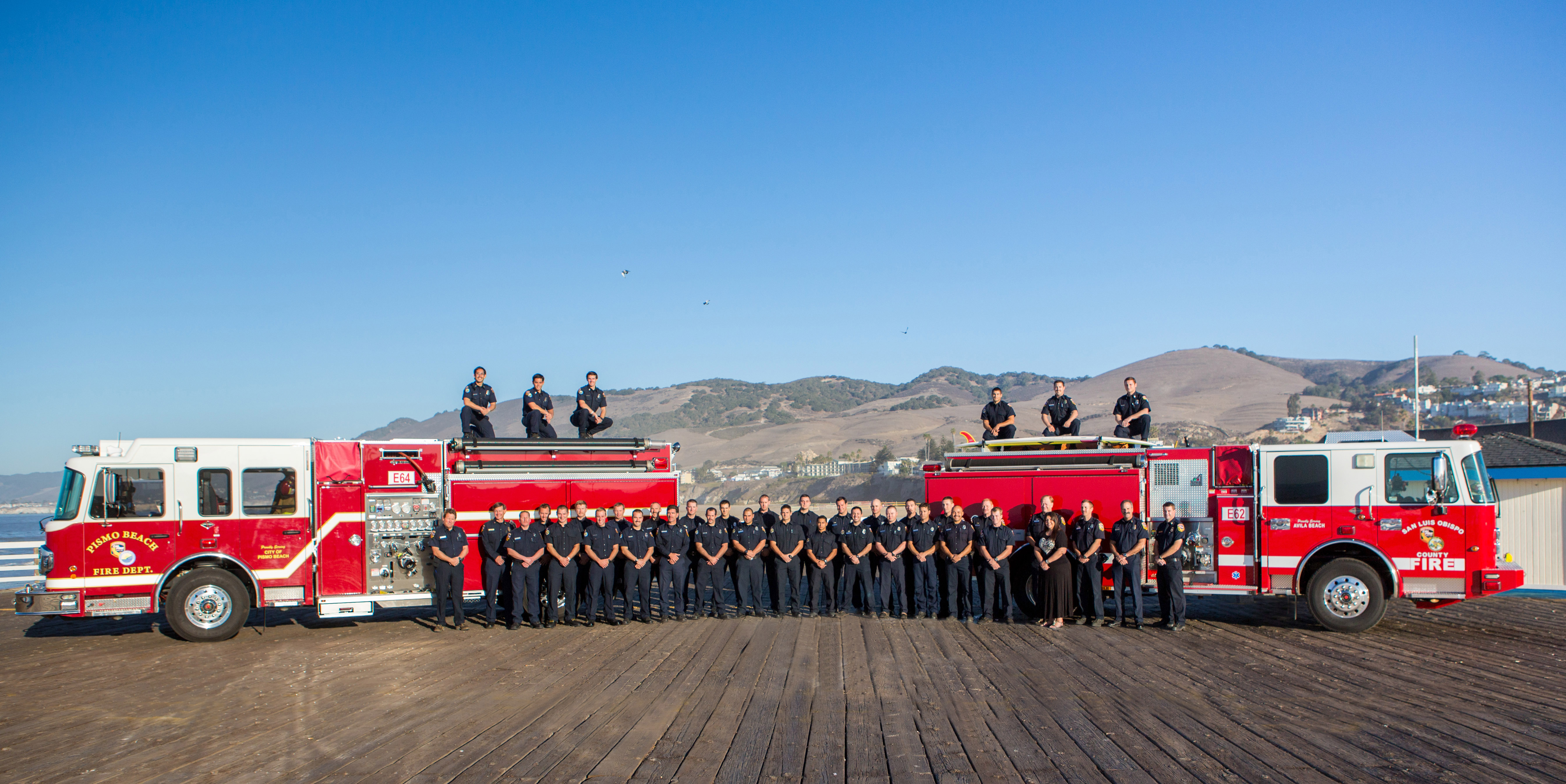 Firefighters line up in front of 2 fire trucks
